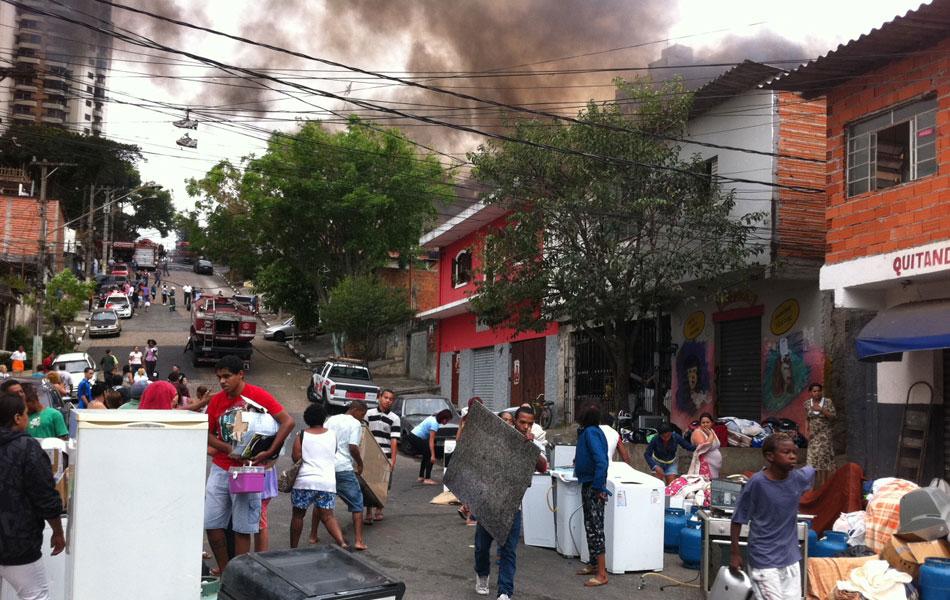 Moradores retiram eletrodomésticos de dentro dos barracos atingidos pelas chamas