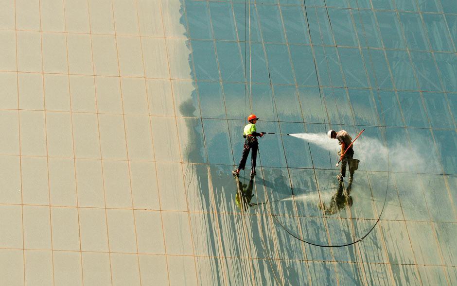 Operário vira alvo de jato d'água de colega enquanto os dois limpam as janelas do Shopping Eldorado, em São Paulo. O tempo seco continua afetando a capital paulista.