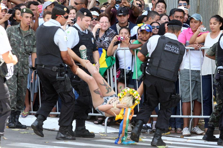 Ativista do grupo feminista Femen tira a blusa e exibe cartaz de protesto ao invadir a pista onde acontecem os desfiles de 7 de Setembro na Esplanada dos Ministérios, em Brasília. Duas ativistas foram presas.