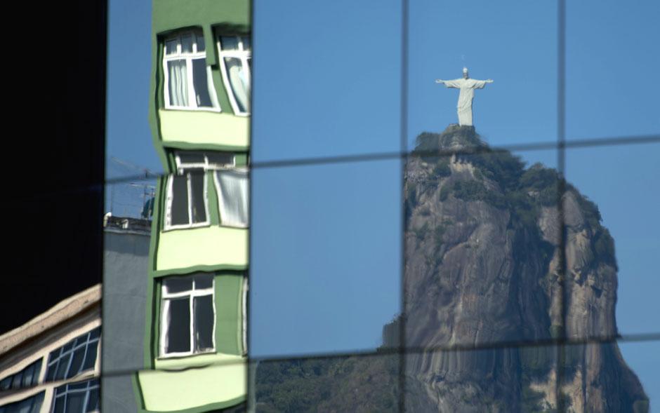 O Cristo Redentor e prédios do Rio de Janeiro são vistos refletidos nas janelas espelhadas de um edifício.