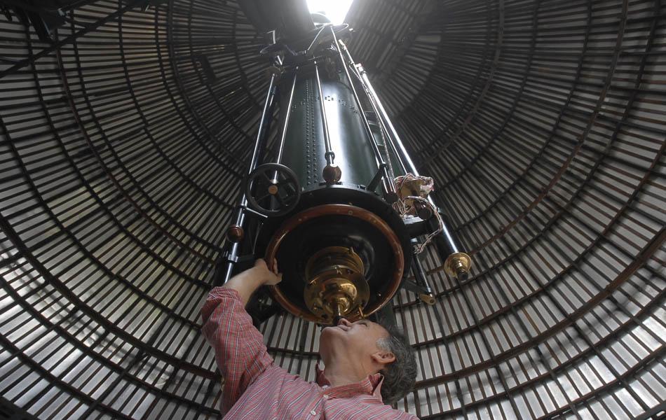 O chefe da Divisão de Atividades Educacionais do observatório, Carlos Henrique Veiga, posa com o maior telescópio do país, que completa 90 anos. A luneta foi adquirida em 1911, mas chegou ao Brasil somente em 1921.