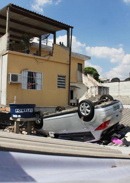 Carro cai de uma garagem de aproximadamente 7 metros de altura sobre uma casa vizinha em Osasco (SP), nesta quinta-feira (18). Mãe e filho estavam dentro do carro no momento da queda, a criança não teve ferimentos e mãe foi levada para o hospital.