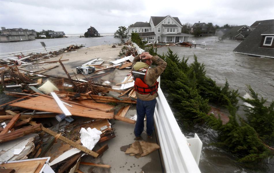 30 de outubro - Brian Hajeski, 41 anos, de Brick, Nova Jersey, reage ao olhar para os restos de uma casa levada pela inundação.