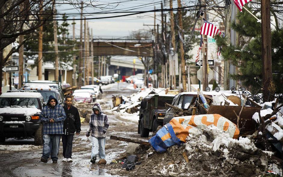 8 de novembro - Jovens caminham por uma via coberta de destroços deixados pela passagem da supertempestade Sandy e pela neve caída esta semana perto da praia de Rockaway, no Queens, em Nova York
