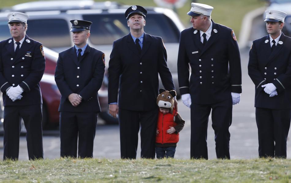 19 de dezembro - Criança aparece fica entre bombeiros no funeral da vítima Daniel Gerard Barden, em Newtown, em Connecticut.