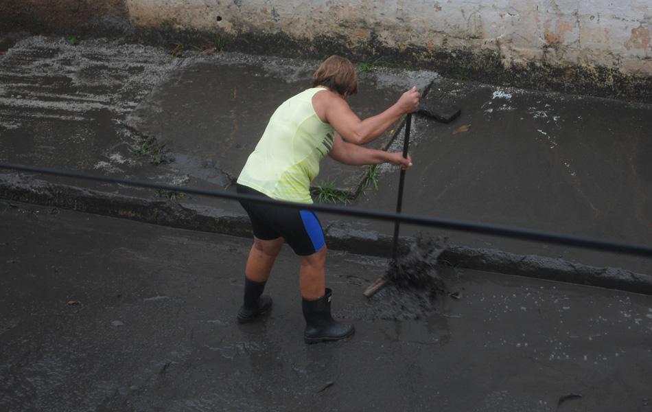 Mulher limpa rua após enchente em Duque de Caxias