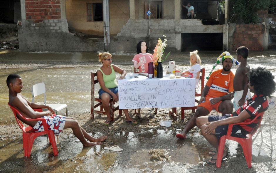 8 de janeiro - Famílias de Xerém, em Duque de Caxias (RJ), tomam café em meio aos estragos causados pela enchente. A cidade foi atingida por um temporal na última quinta-feira (3). Milhares de pessoas ficaram sem abastecimento de água em casa