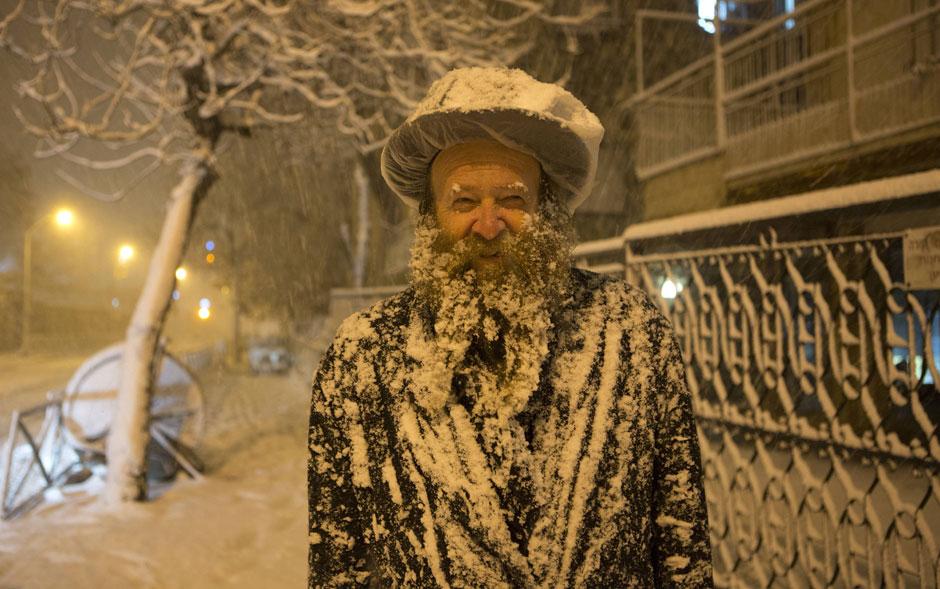 Judeu ultra-ortodoxo sorri coberto por camada de neve durante nevasca em Jerusalém