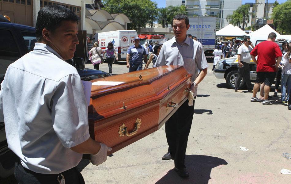 27 de janeiro - Funcionários de funerária carregam caixão com corpo de vítima de incêndio em Santa Maria