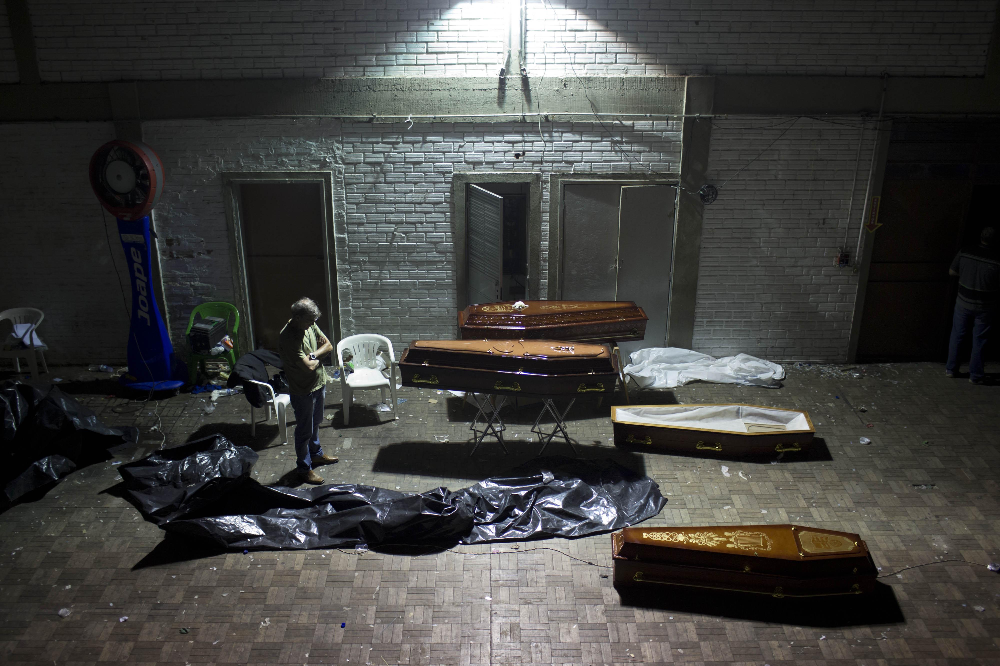 27 de janeiro - Homem olha para caixões com corpos de vítimas do incêndio na boate Kiss, onde mais de 200 pessoas morreram no domingo, 27, em Santa Maria (RS).