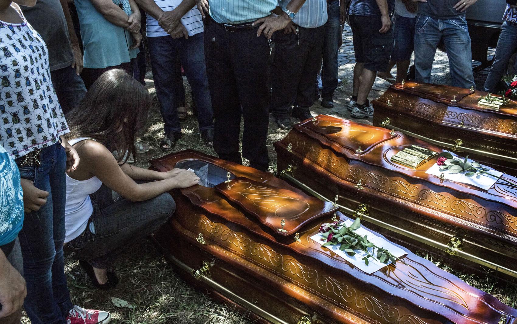 28 de janeiro - Parente de três vítimas da tragédia chora sobre caixões durante enterro em Santa Maria