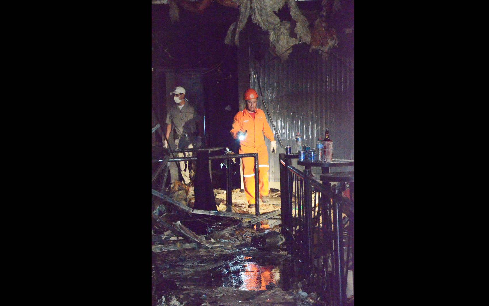 Bombeiros no interior da boate Kiss durante vistoria após o resgate