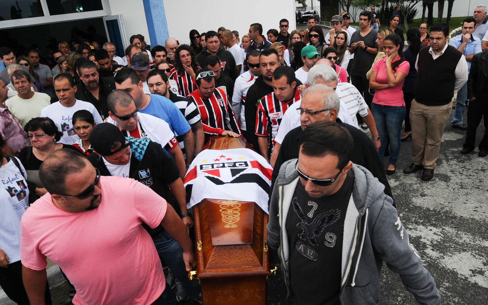 Homens carregam caixão durante o funeral de Rafael Paulo Nunes de Carvalho, de 32 anos, no Cemitério das Lágrimas, em São Caetano do Sul (SP). Ele foi uma das vítimas do incêndio em Santa Maria (RS), para onde tinha viajado para comemorar seu aniversário.
