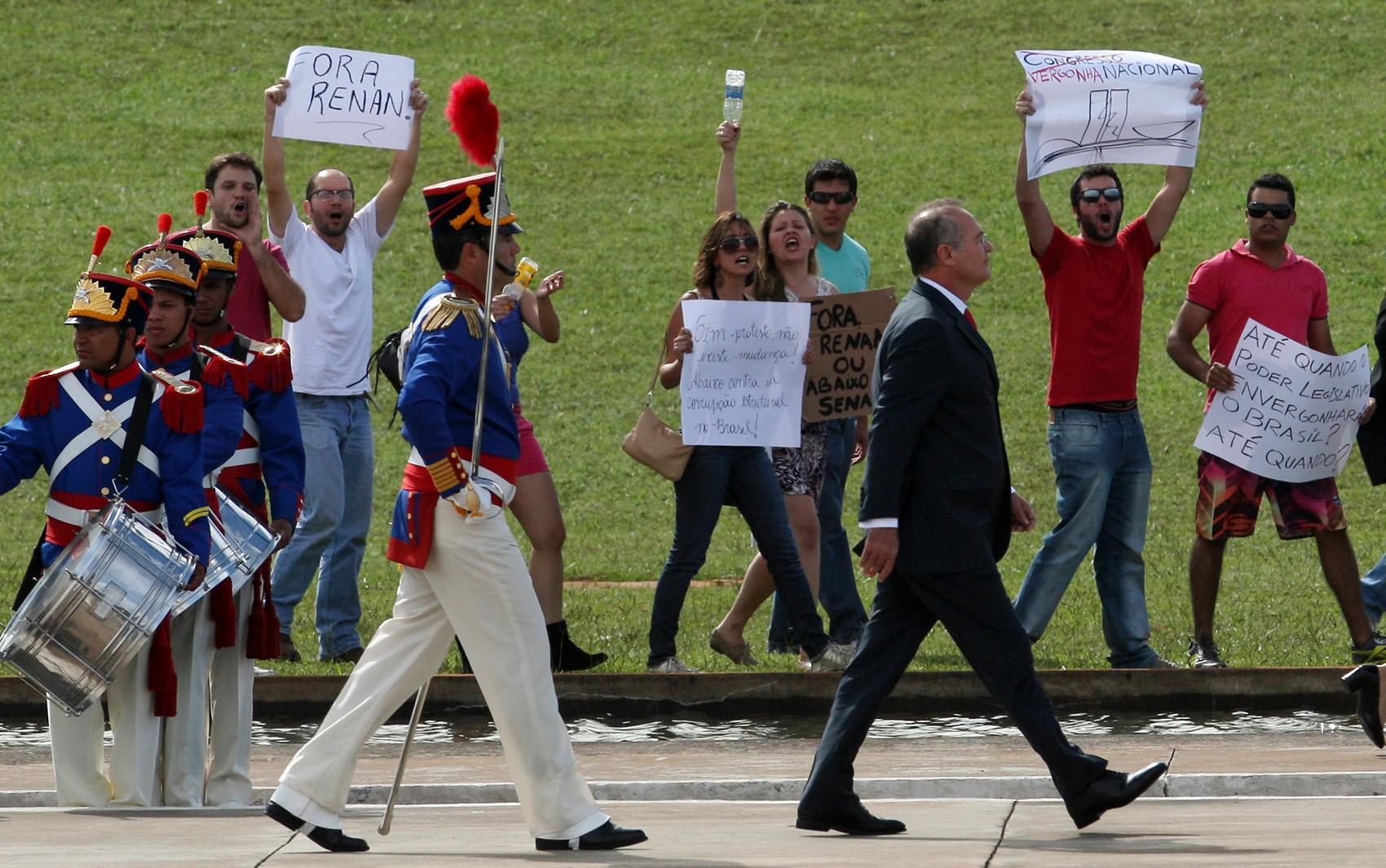 Populares protestam durante passagem do presidente do Senado, Renan Calheiros, em revista a tropa momentos antes da abertura oficial   dos trabalhos no Congresso Nacional, em Brasília, nesta segunda-feira (4).
