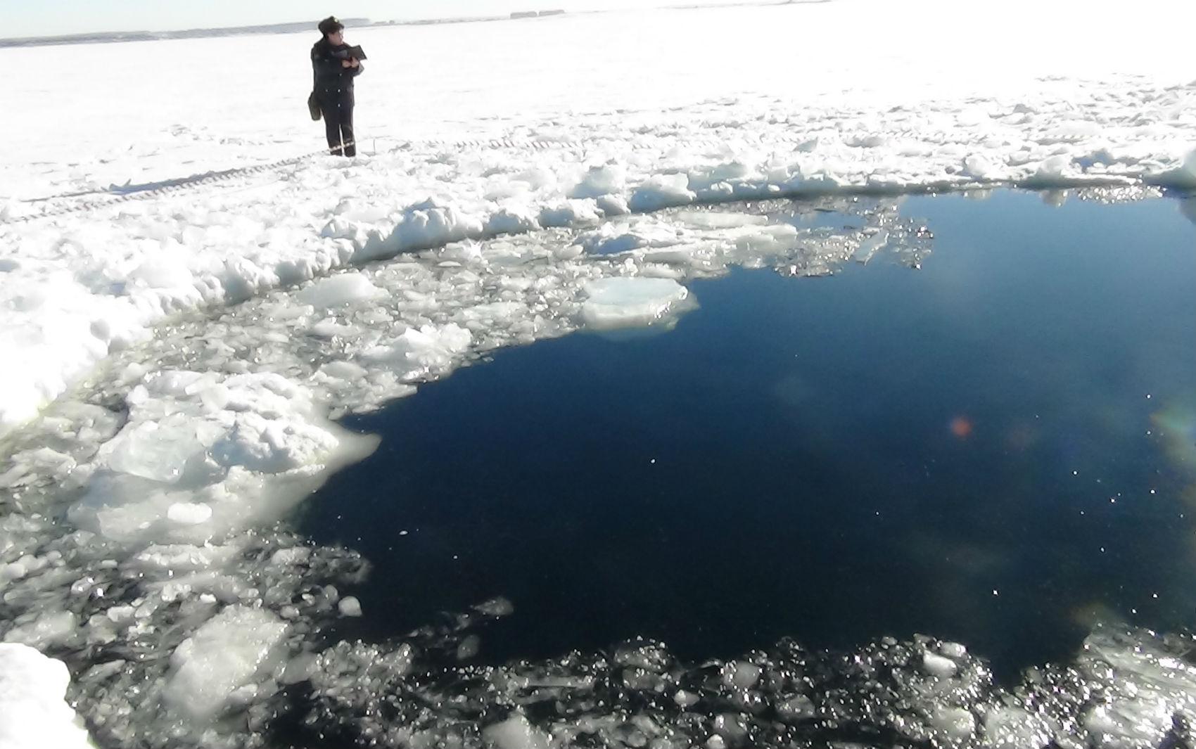 Pessoa observa buraco provocado por suposto meteorito em lago congelado Chebarkul na Rússia.