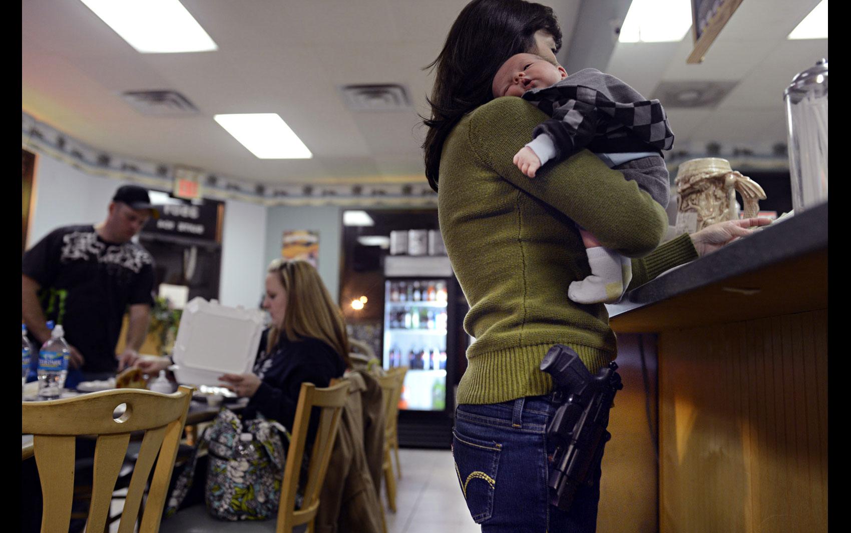 Com o filho de duas semanas de idade no colo e uma pistola à cintura, mulher paga a conta na pizzaria All Around, em Virginia Beach. O local oferece 15% de desconto para clientes portando armas ou que apresentem a permissão ao porte.