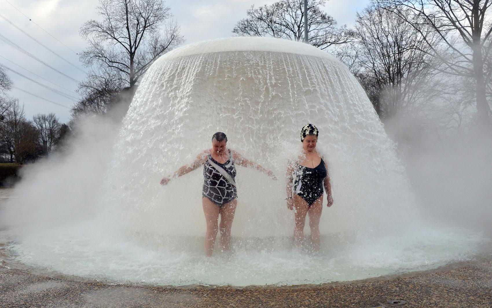 Mulheres se banham na fonte recreativa Sonnenbad ('banho de sol', em alemão), a temperatura ambiente pouco abaixo de 0° C, na reabertura do espaço em Karlsruhe, Alemanha. É o primeiro espaço recreativo com água a reabrir na cidade após fechar no inverno.
