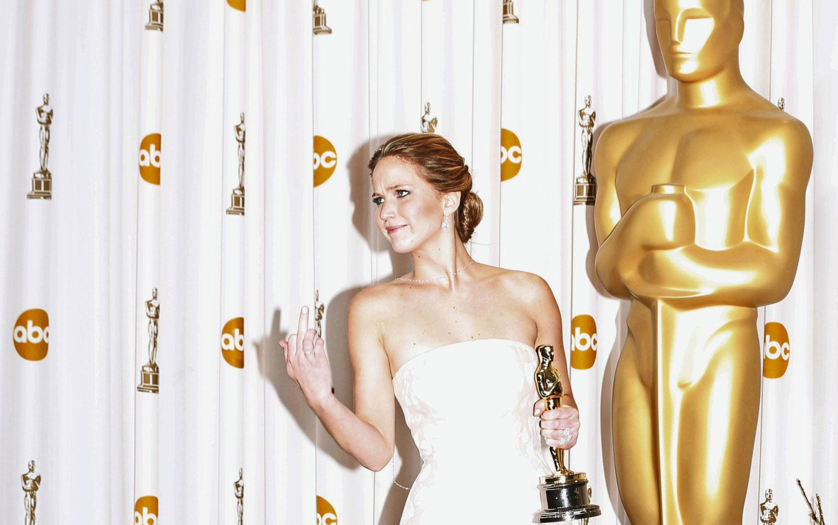 Após levar a estatueta de Melhor Atriz e tomar um tombo ao subir no palco, Jennifer Lawrence reage às piadas de fotógrafos alertando-a para ter atenção com os degraus quando ela foi posar para fotos no backstage