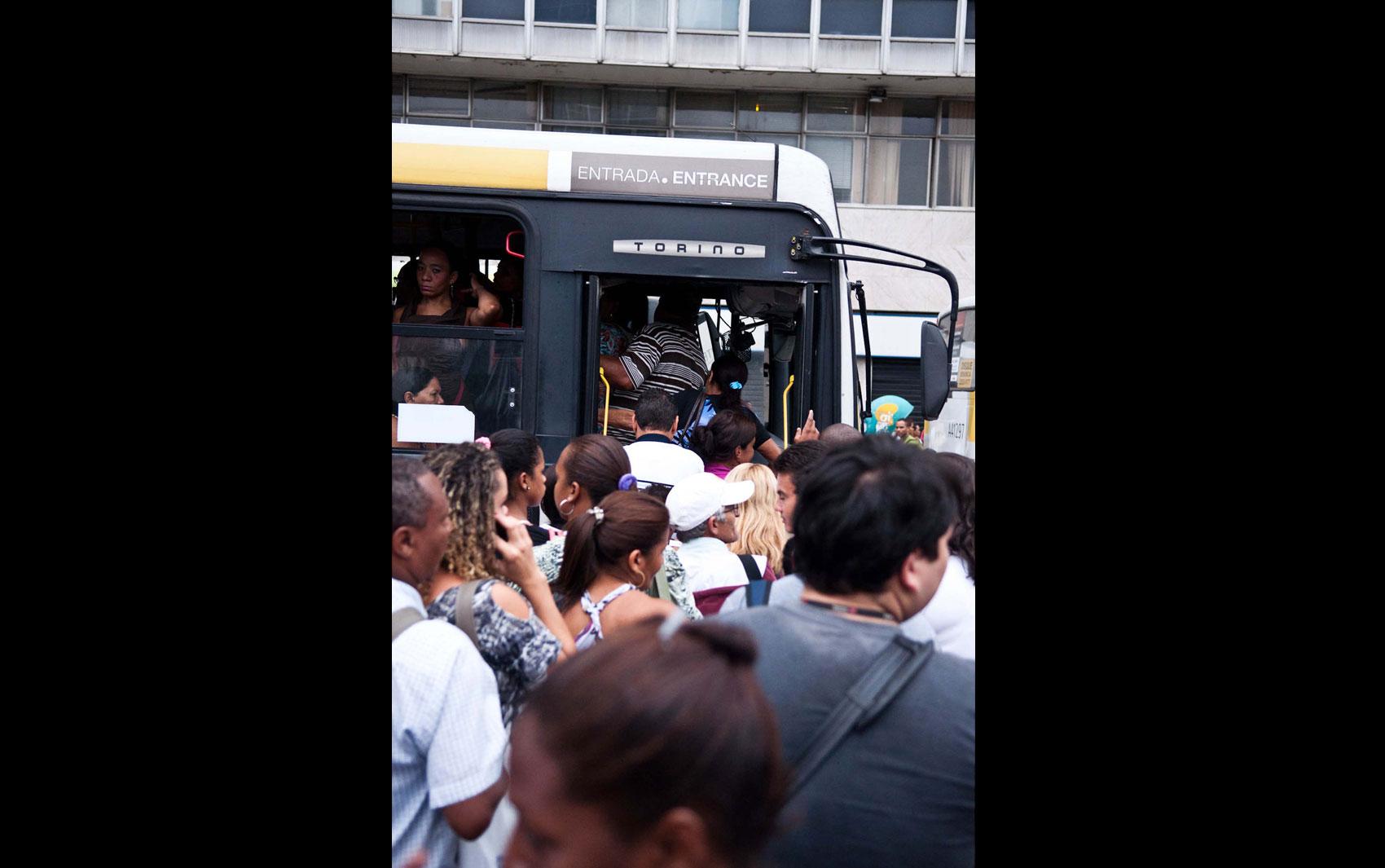 Passageiros disputam espaço na entrada de um ônibus na Central do Brasil