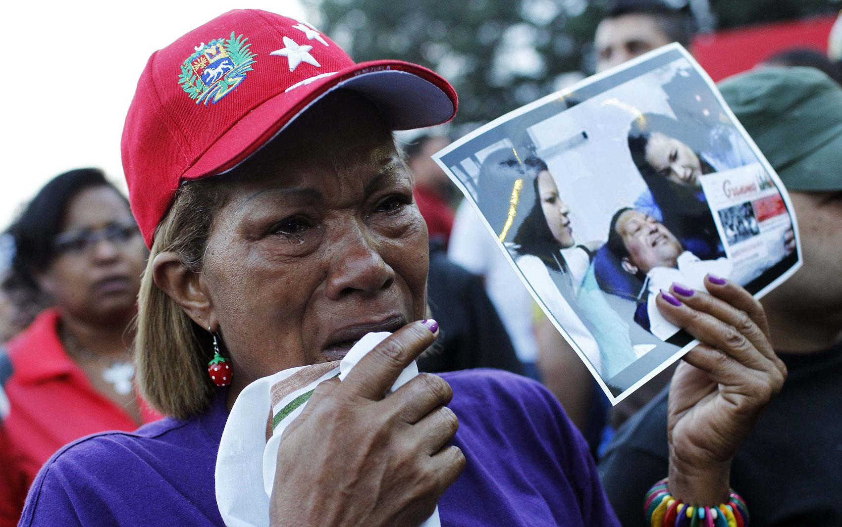 Com foto de Hugo Chávez na mão, venezuelana chora após o anúncio da morte do presidente do país