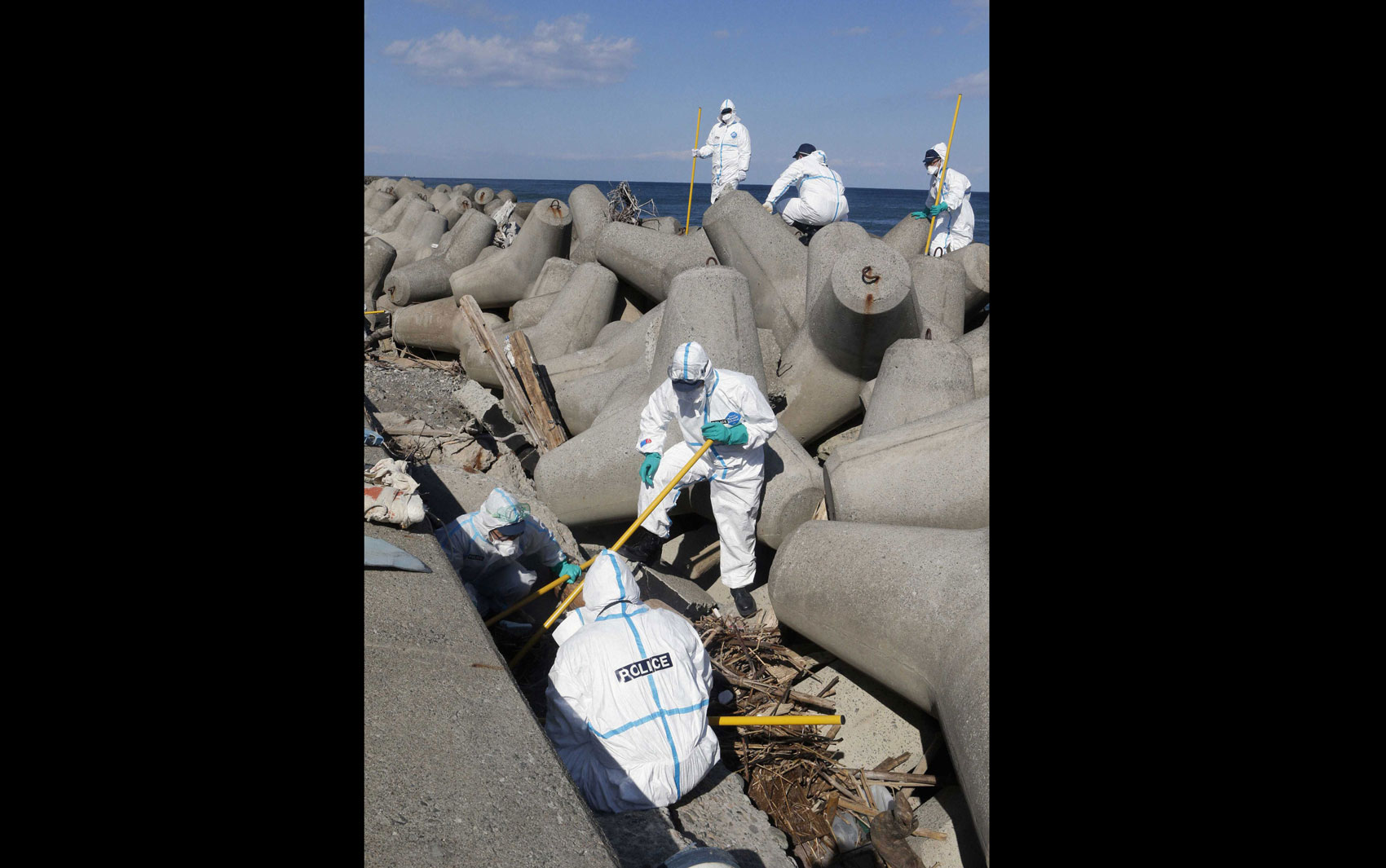 Equipe com trajes de proteção busca por corpos de desaparecidos em Okuma, perto da usina nuclear de Fukushima, exatos dois anos após o tsunami que gerou um sério acidente nuclear no local