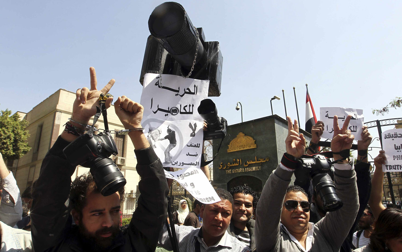 Fotógrafos protestam com as mãos simbolicamente acorrentadas denunciando o tratamento dado a eles pelo governo e pela Irmandade Muçulmana na cobertura de fatos recentes, no Cairo, Egito.