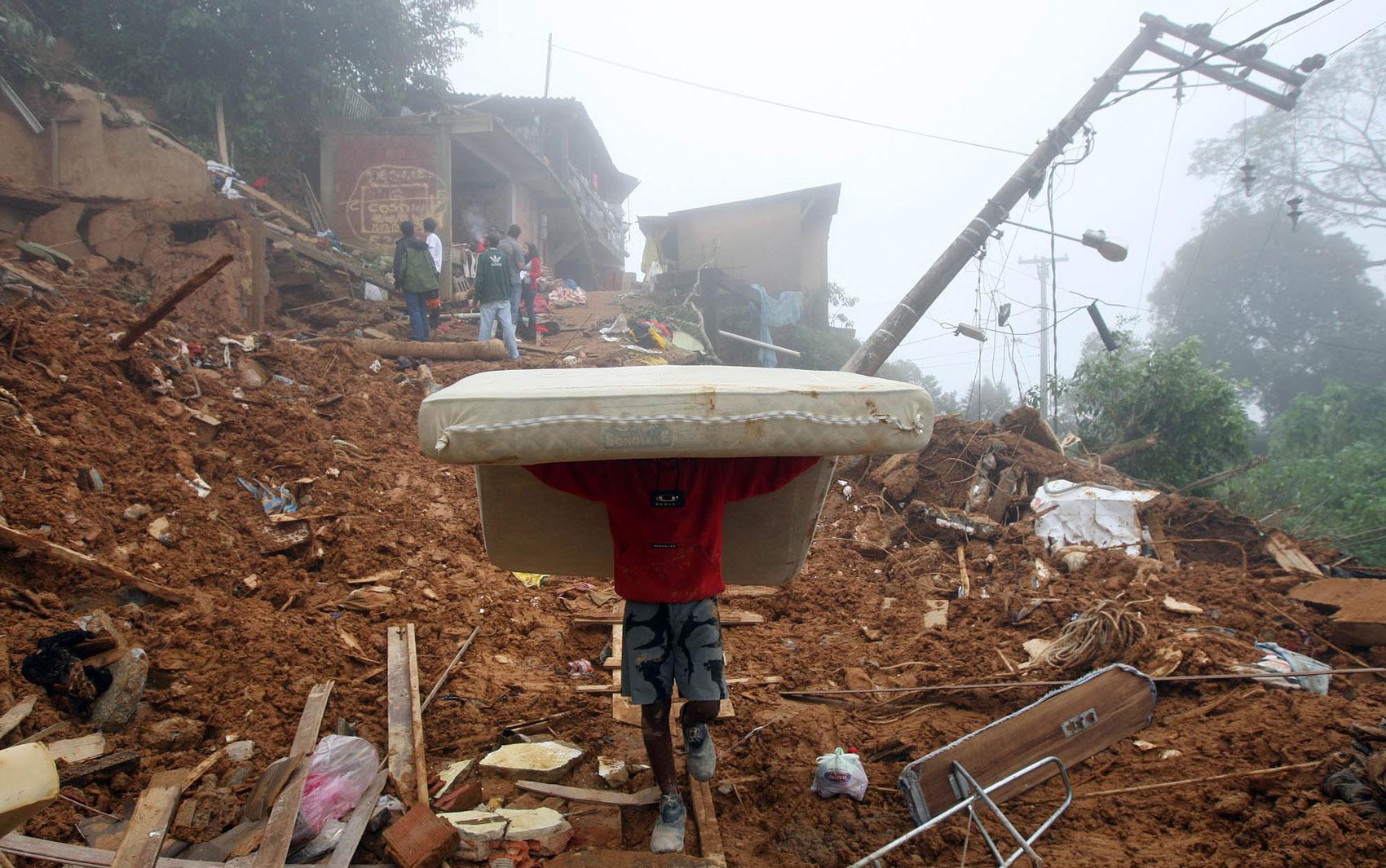 20 de março - Moradores retiram pertences de casas atingidas por deslizamento na rua Caminho do Imperador, em Alto Independência, Petrópolis