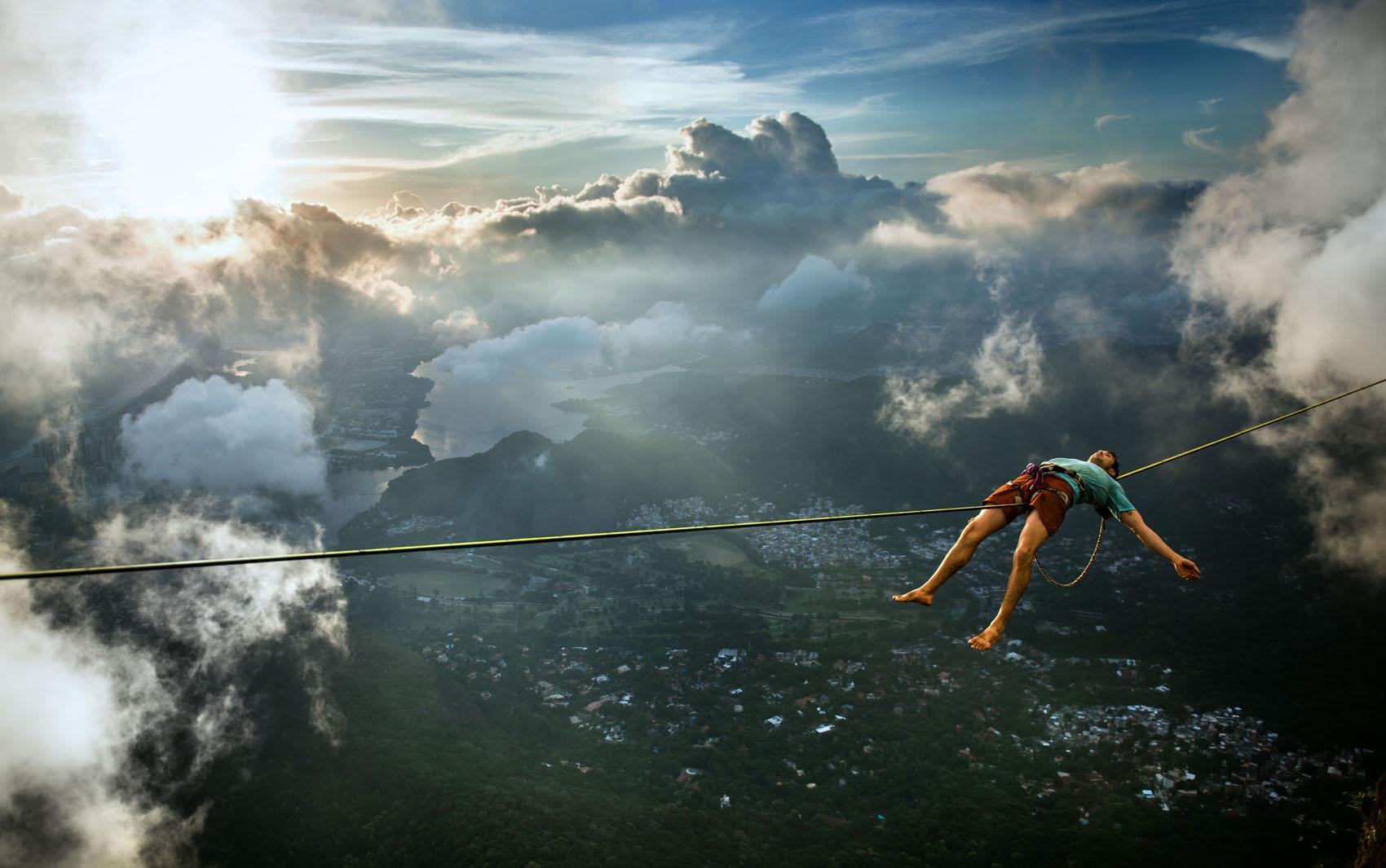 Brian Mosbaugh descansa durante travessia em corda instalada na Pedra da Gávea no Rio de Janeiro, quase 3 mil metros acima do mar.