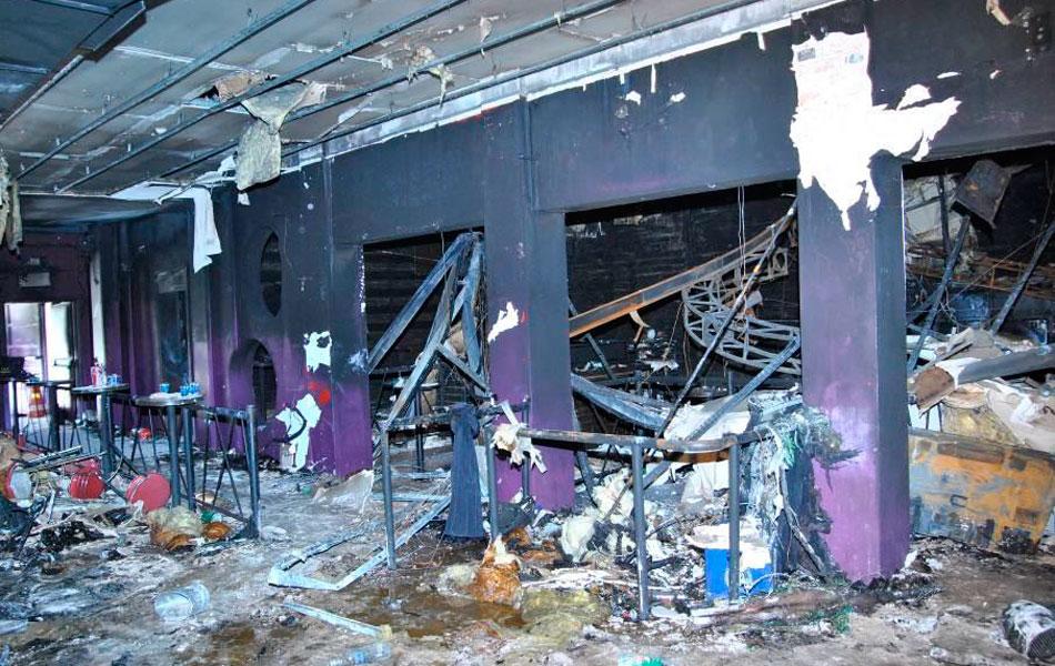 Vista do salão central da boate Kiss após o incêndio, o principal corredor de acesso à porta de saída