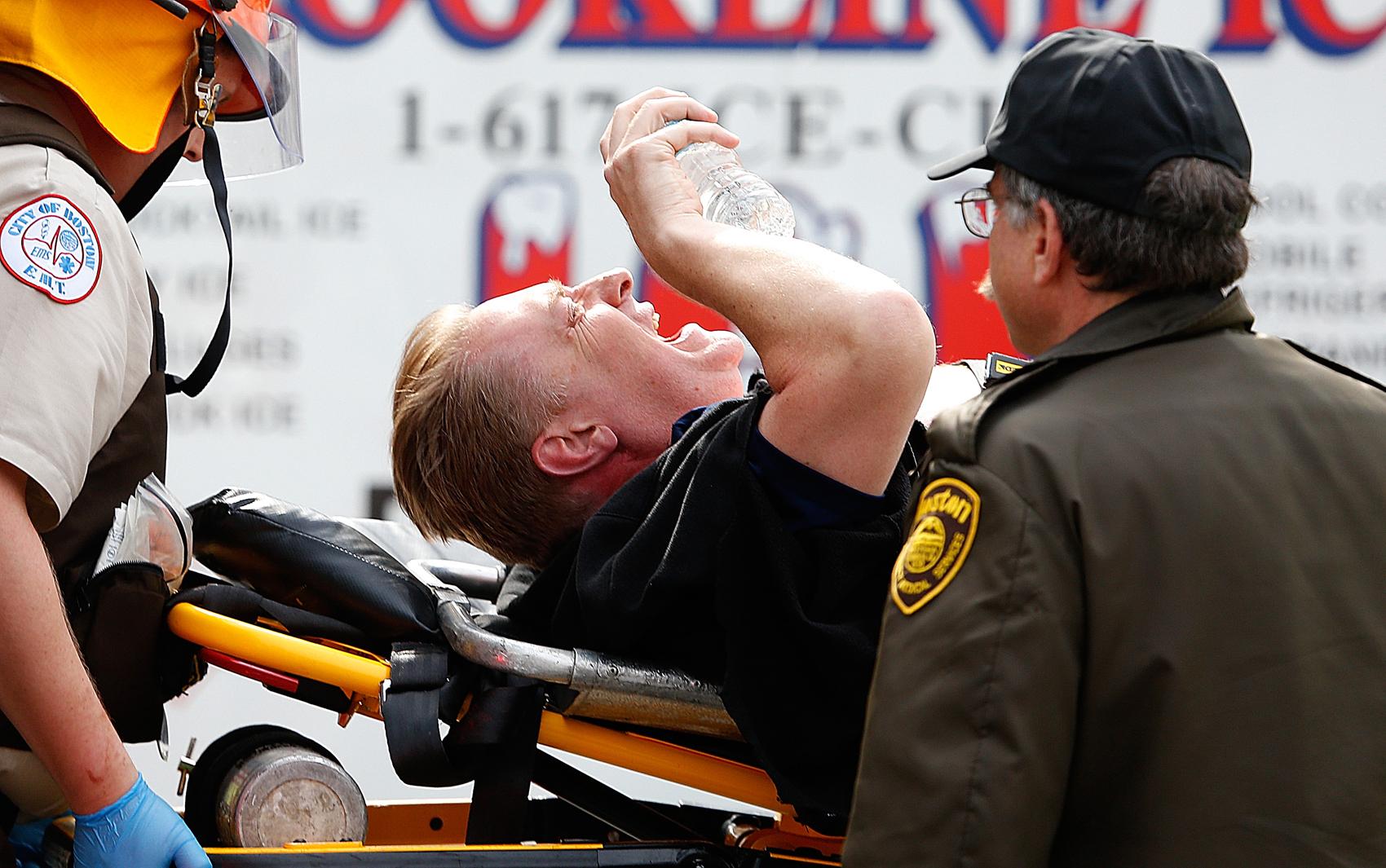 Ferido é levado para ambulância depois de explosões deixarem duas pessoas mortas.