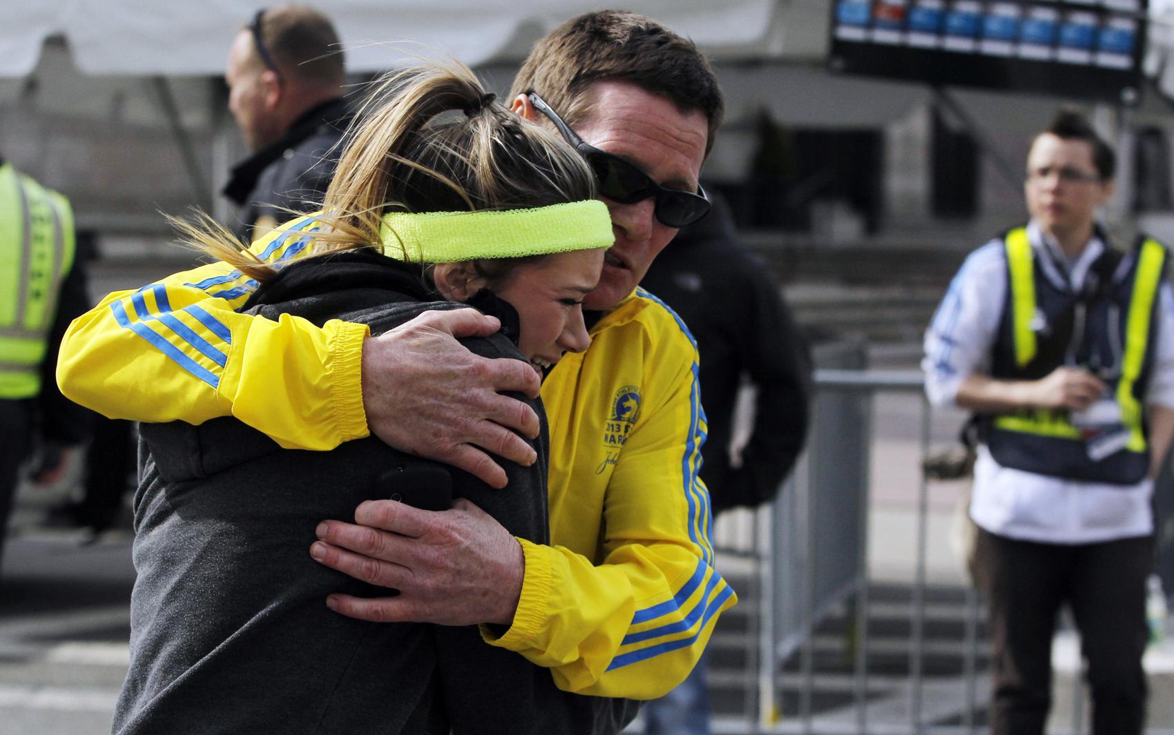 Atleta é amparada por homem depois de explosões durante a maratona nos EUA.