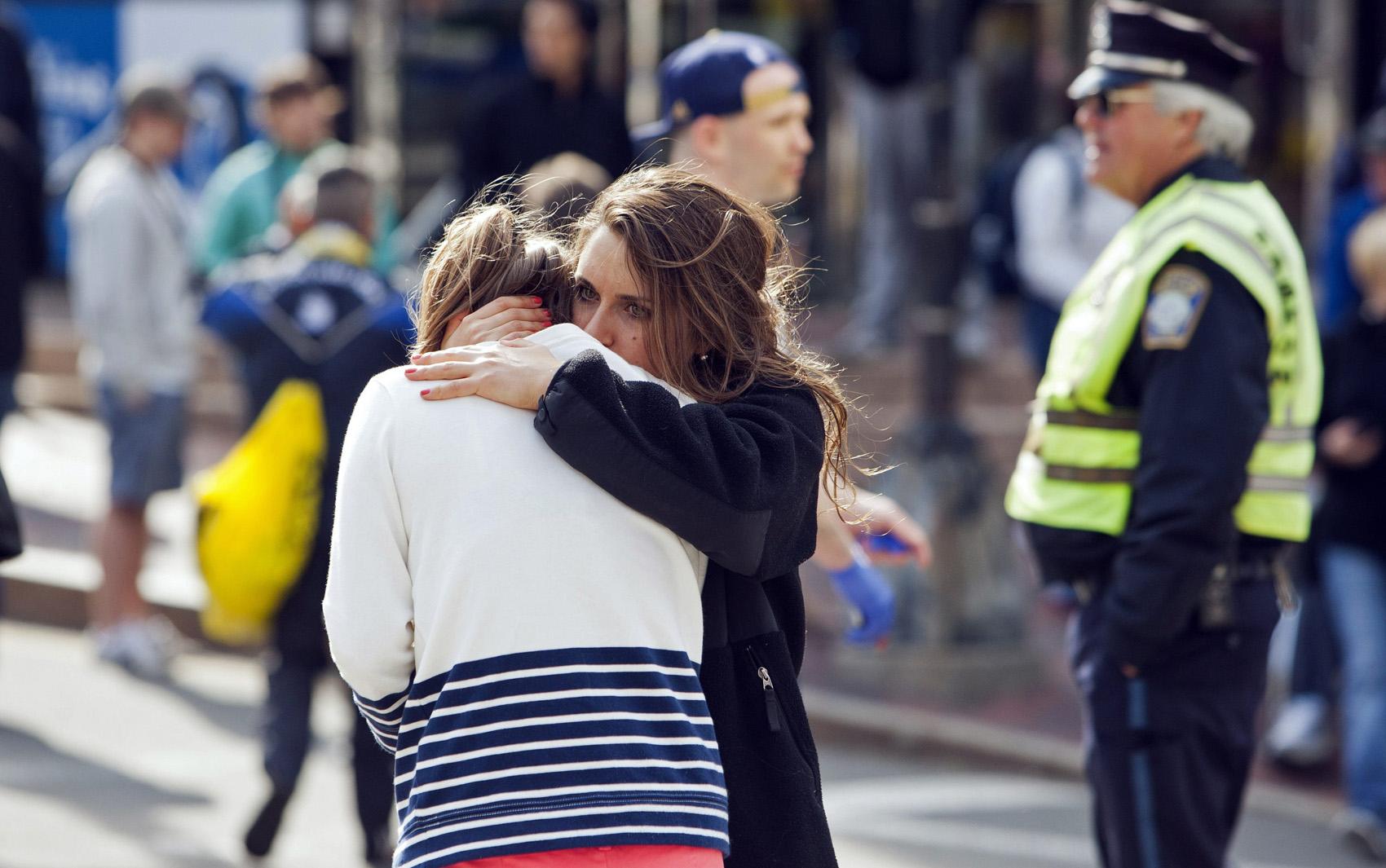 Meninas se abraçam próximo ao local das explosões em Boston.