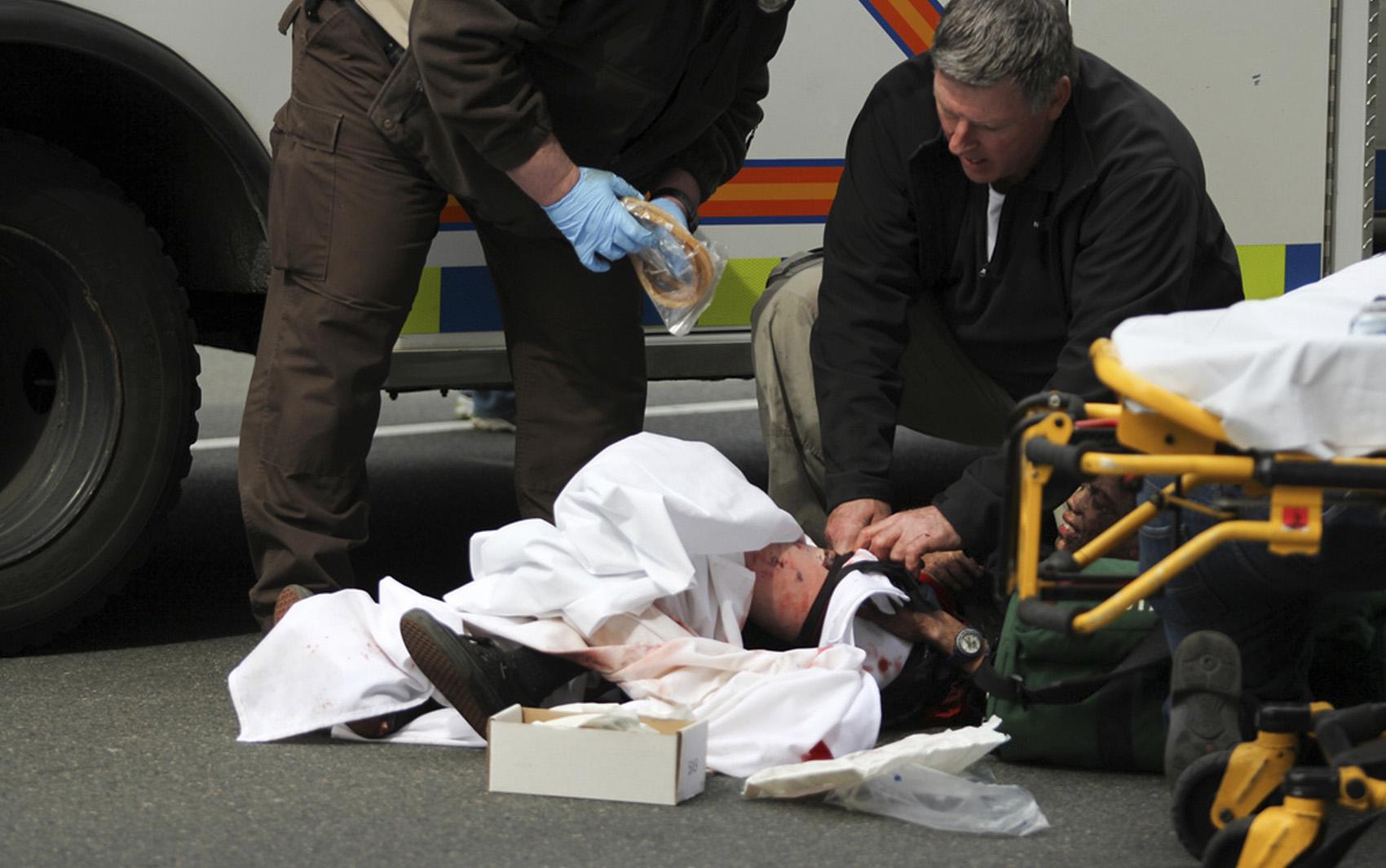 Ferido durante a explosão recebe primeiros socorros no local onde acontecia a maratona.