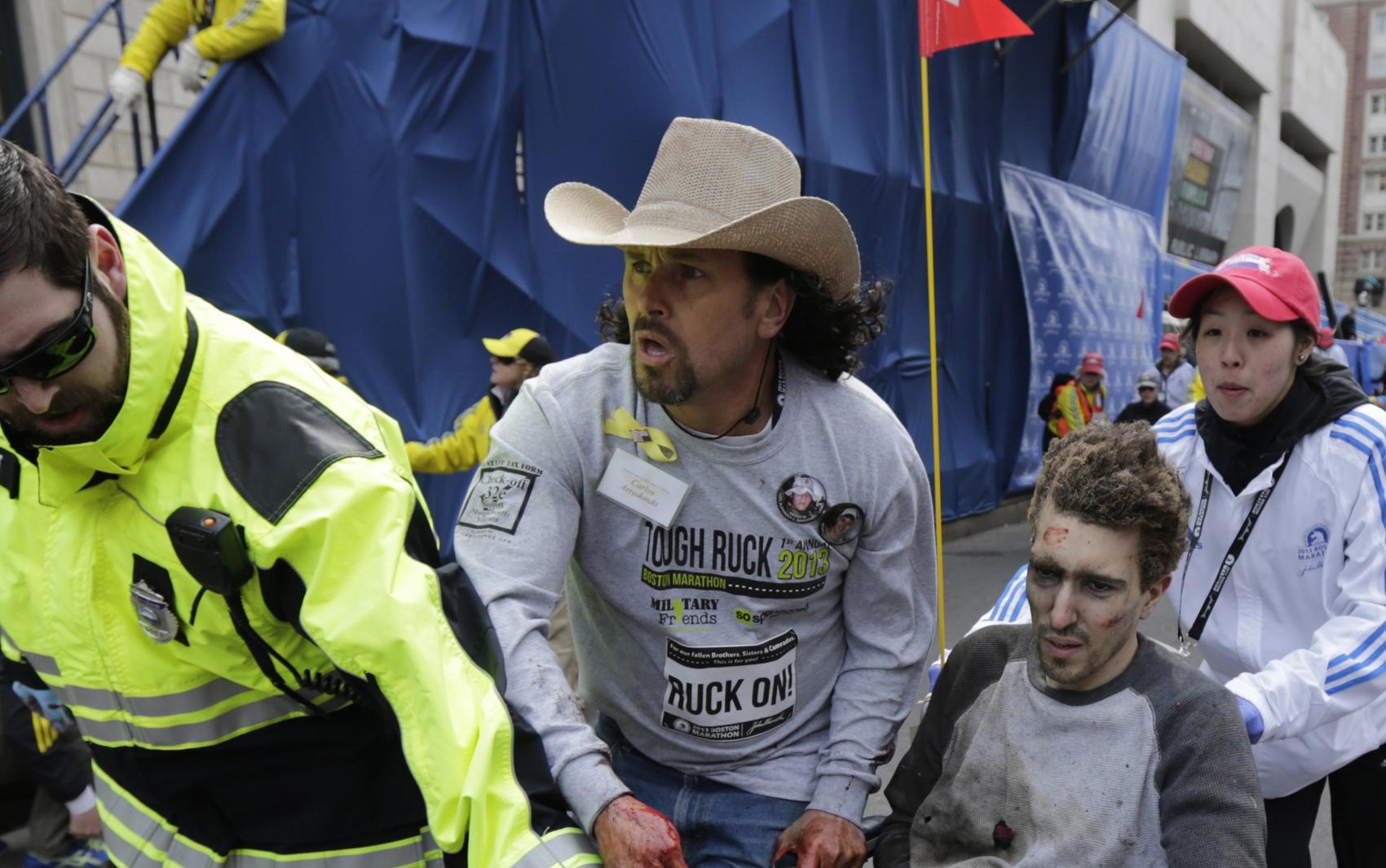Homem recebe primeiros atendimentos depois da explosão em Boston.