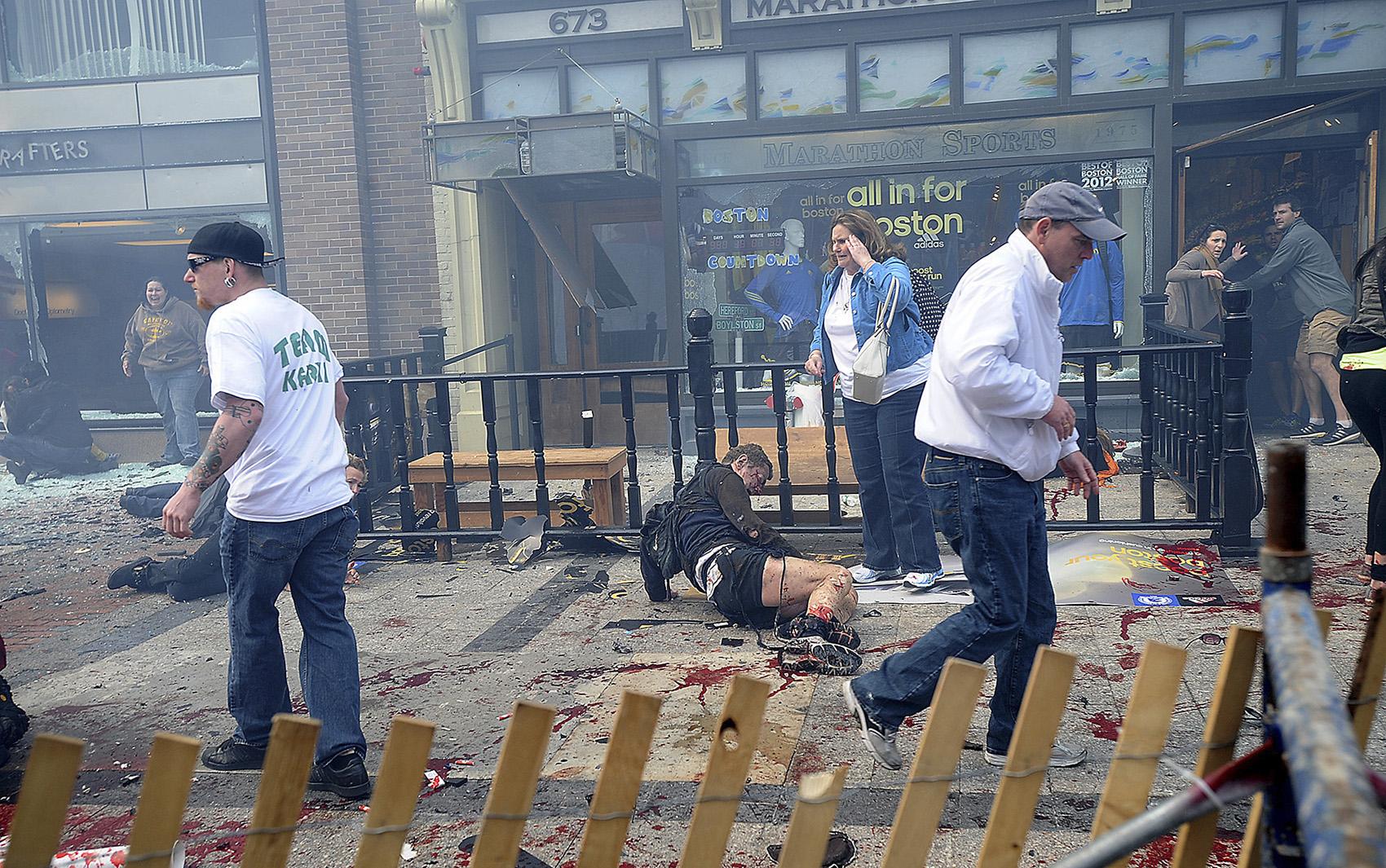 Ferido aguarda socorro momentos após a explosão em Boston.