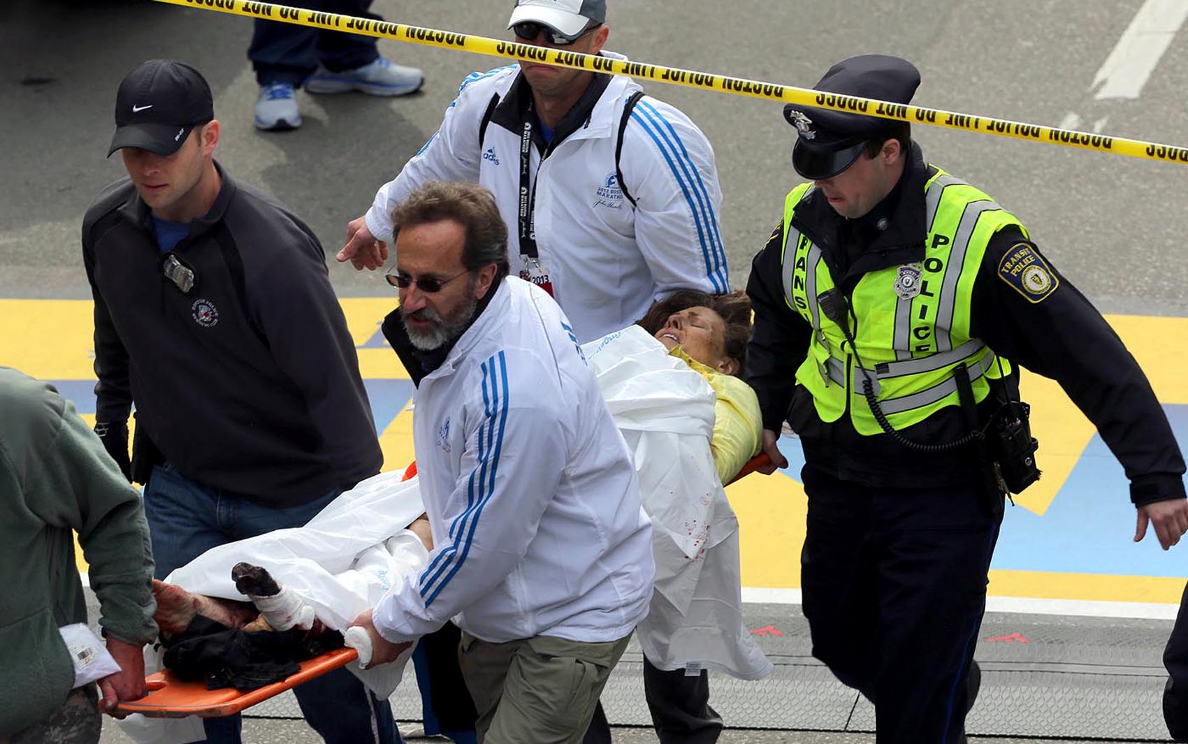 Mulher ferida em explosão recebe atendimento médico em Boston.