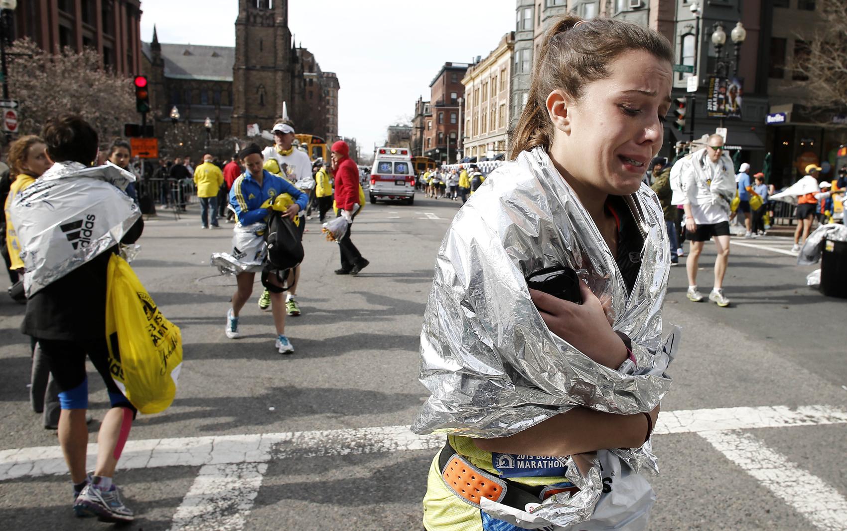 Atleta deixa maratona chorando após explosões perto da linha de chegada em Boston.