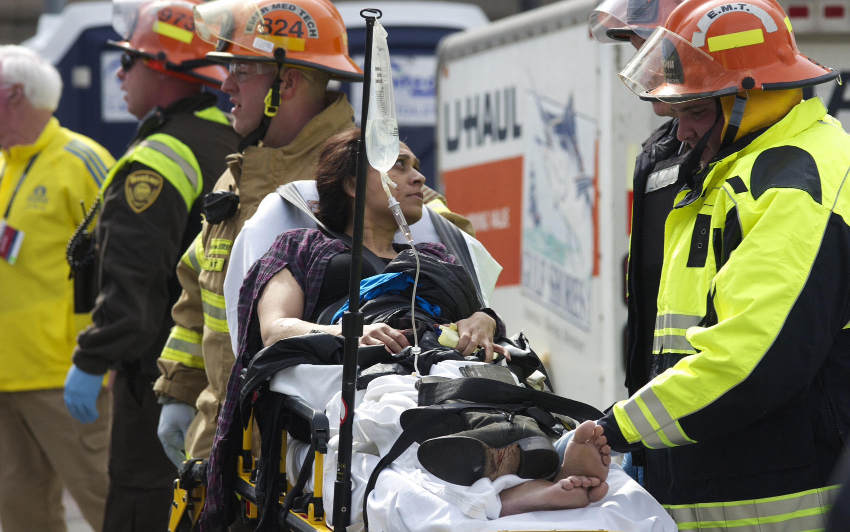 Mulher aguarda para ser levada de ambulância do local do acidente.