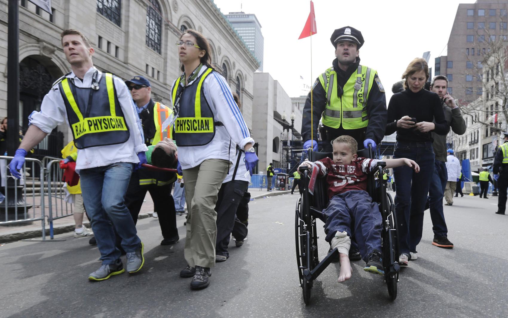 Garoto ferido na explosão é levado de cadeira de rodas por equipes de emergência.