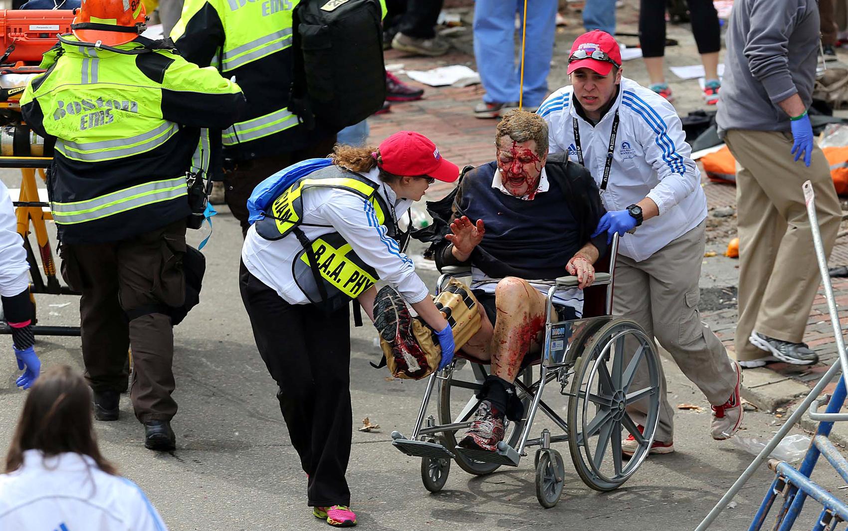 Homem é auxiliado por socorristas após explosão na Maratona de Boston.
