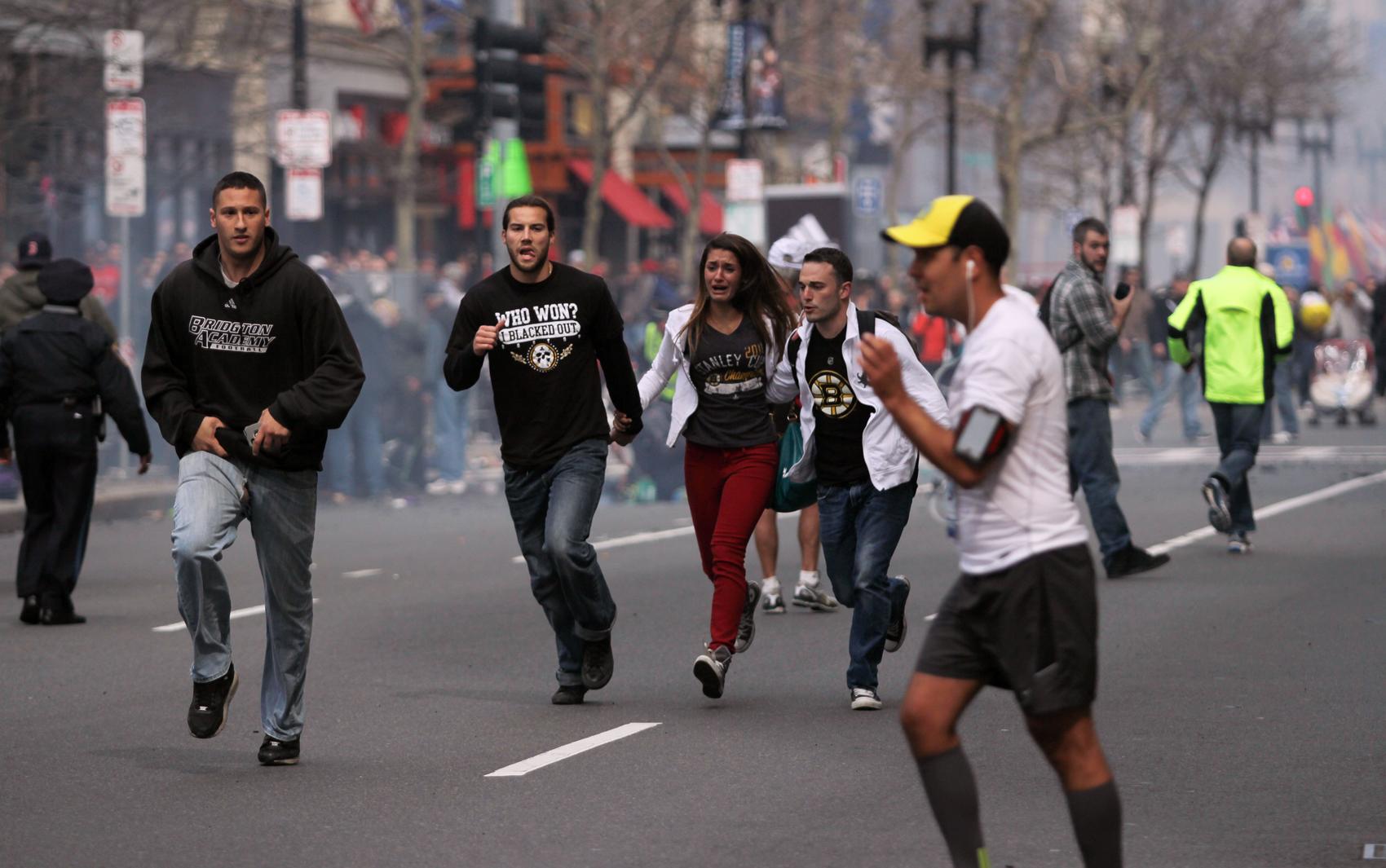 Pessoas que assistiam a maratona deixam correndo local próximo da explosão.