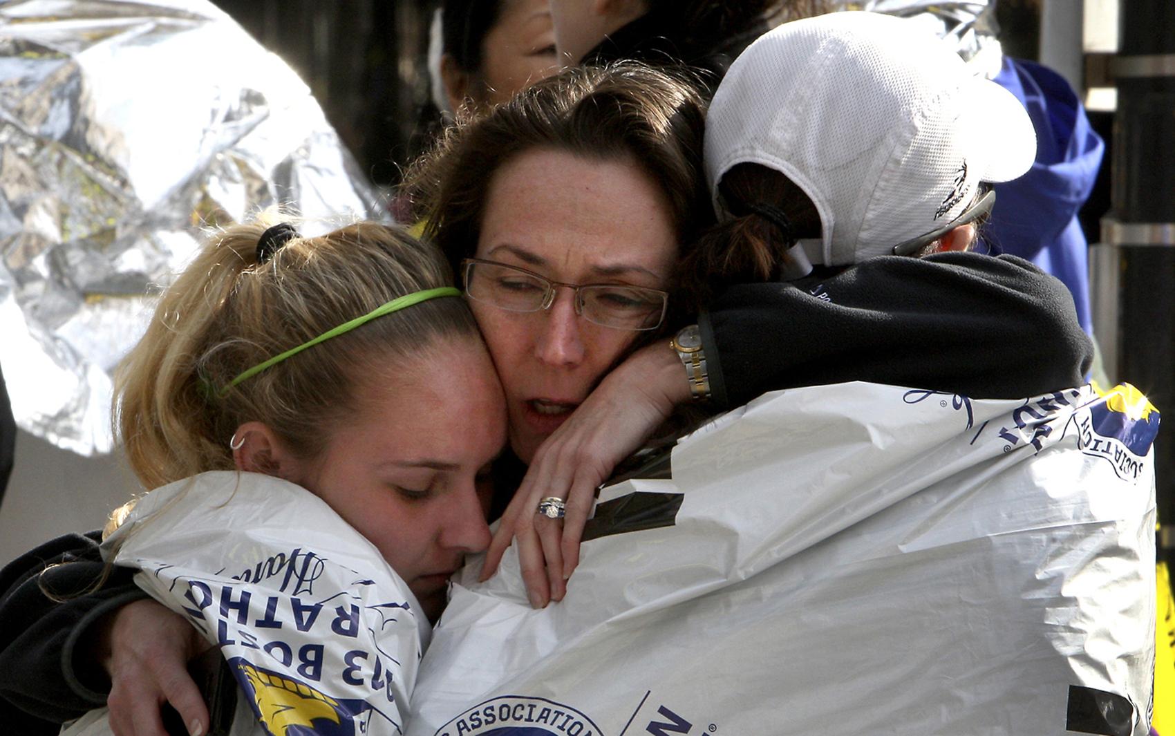 Mulher abraça seus familiares ao encontrá-los depois das explosões em Boston.