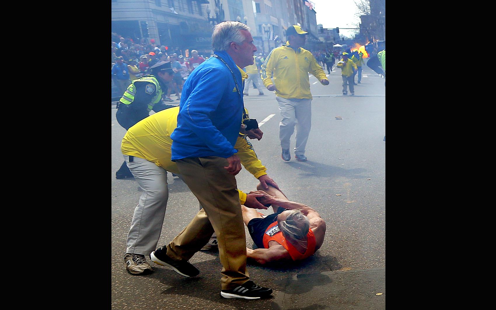 Atleta caído é socorrido pela organização da prova depois de explosão próxima da linha de chegada da maratona de Boston.