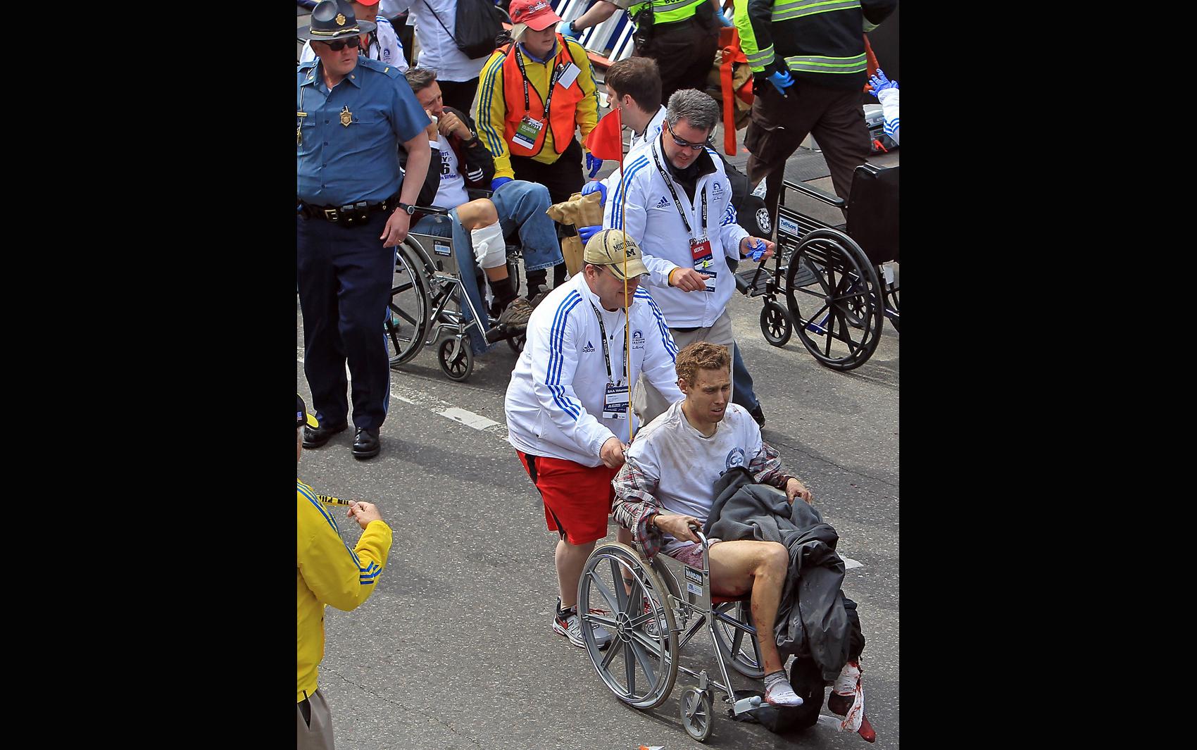 Feridos na explosão na Maratona de Boston são socorridos em cadeiras de roda.