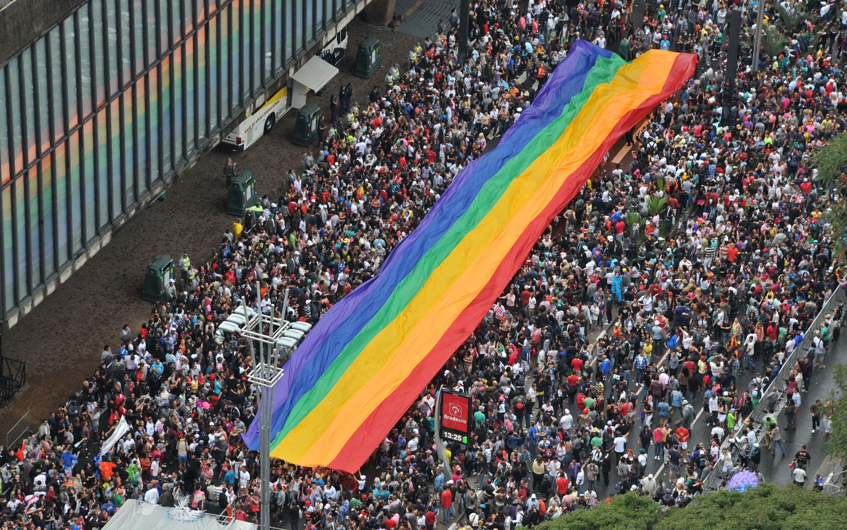 Bandeira com as cores do orgulho gay é estendida pelo público durante o desfile na Parada Gay neste domingo (2)