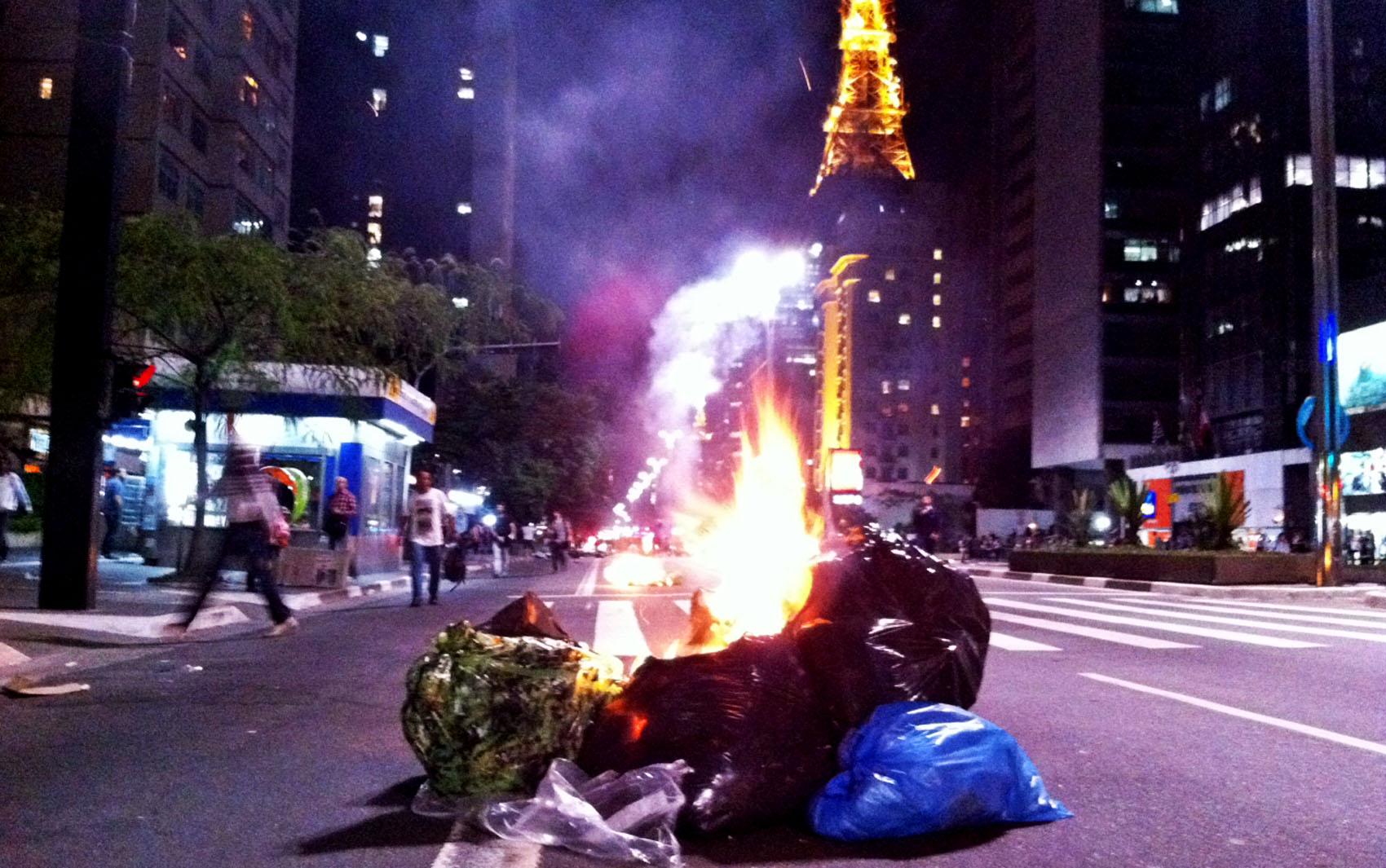 Manifestantes colocam fogo em lixo em uma das pistas da Av. Paulista