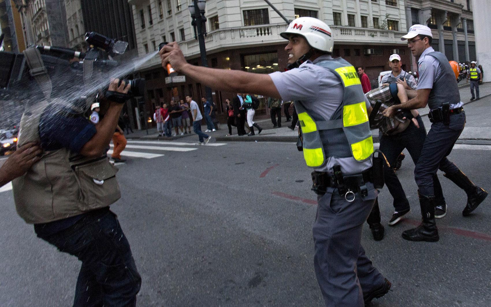 Policial usa spray de pimenta contra manifestantes próximo de um cinegrafista durante protesto em São Paulo.