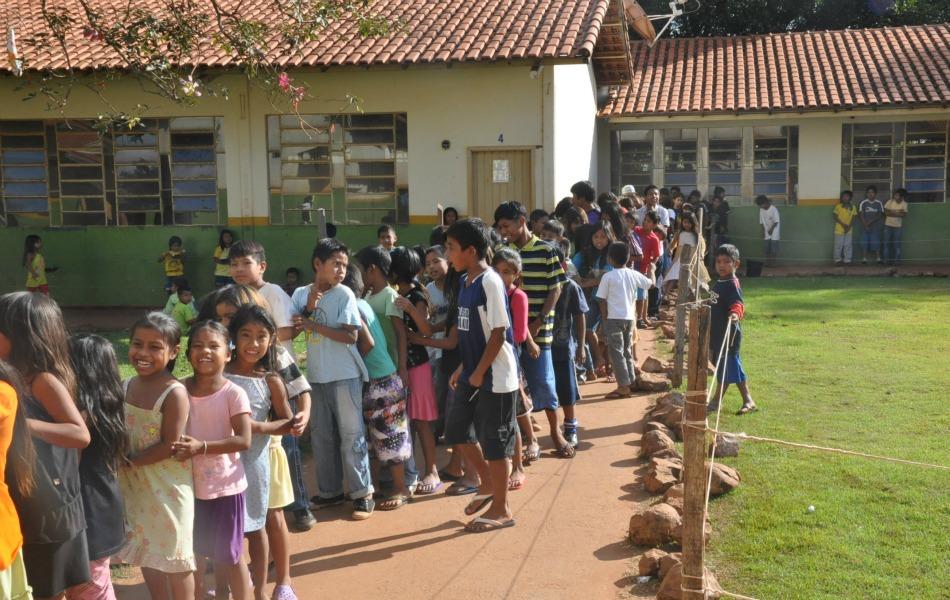 Crianças formam fila para a merenda na escola Ñandejara Pólo, em Caarapó.
