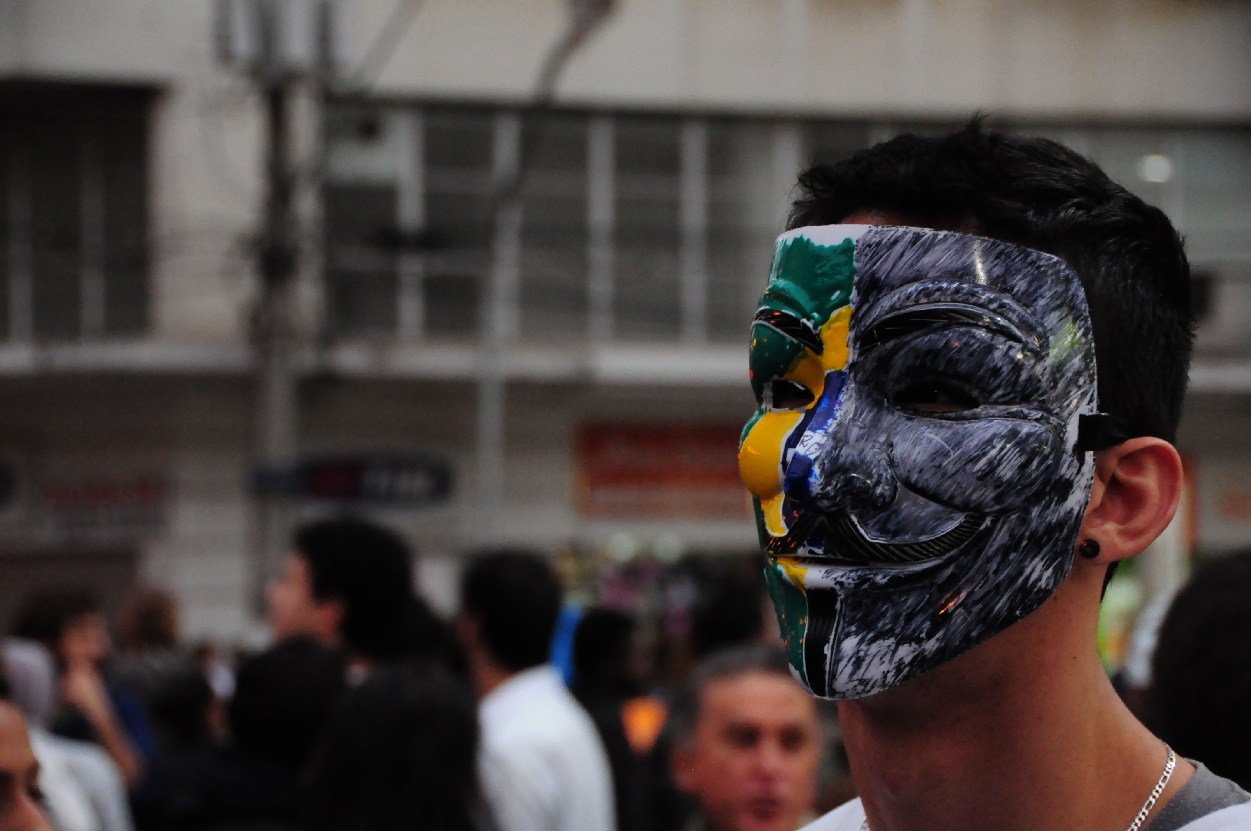Manifestante utiliza máscara com metade da bandeira do Brasil no terceiro dia de protestos