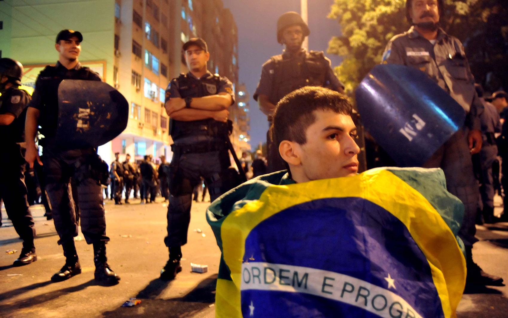 Manifestante senta em frente a barreira policial depois dos protestos próximo ao Maracanã